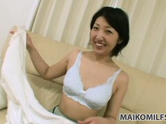 Sexy Asian milf with nice tits sits on the couch pleasing her snatch with a vibrator