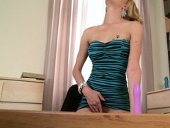 Sexy blonde with a great ass lies on the desk pleasing her shaved cunt with a dildo