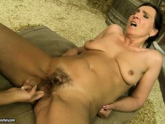 Sexy young lesbian eats out a granny's hairy snatch in a barn