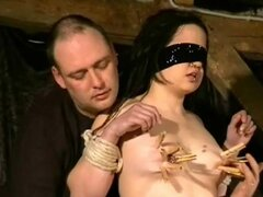 Blindfolded girl in pain during BDSM movie