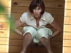 Mature woman is peeing...