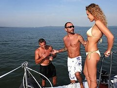 Greg and Colette were enjoying some peace on their yacht when Colette spotted a shipwrecked guy in the water. After they helped him up onto the deck they offered him some first aid: Colette started sucking on both erect cocks for a start and then let the