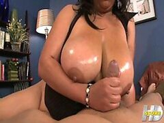 A BBW Latina beauty is covered in oil to use her juicy juggs to toy with his tool