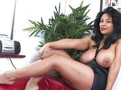 Alluring dark haired milf with huge honkers in stockings stripping and posing