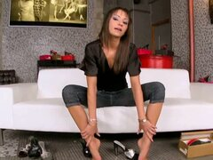 Sexy brunette plays with her feet and her fanny