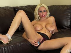 On her knees on the sofa, Holly sticks a blue dildo in her snatch from behind