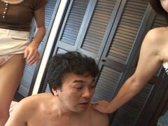 One japanese babe sits on his face, the other jerks him off
