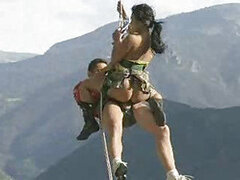A ridiculously randy couple that love riding in random places fuck in a harness while climbing