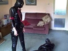 Karen Chessman is totally encased in rubber including a gasmask and is lying bound in ropes on the floor Adreena is dressed from head to toes in skintight latex and is wearing black thigh bootd She circles Karen testing her bonds and kicking and