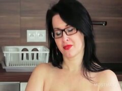 Busty mature in glasses fingers snatch on a chair