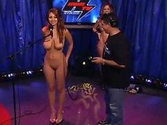 A very random and kinky scene as two naked stunners stand on a TV show stage and sing