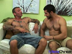 Two buff men make out on the couch then nibble on some sausage