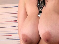Busty brunette bends over to tease the camera with her huge tits