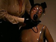 Blonde Dominatrix Makes Busty Submissive Brunette Wear Suffocating Latex Suit