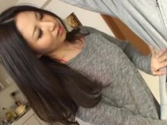 Pretty Japanese girl plays with a cock in the kitchen