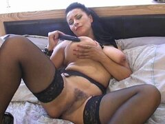 British MILF plays with herself on the bed