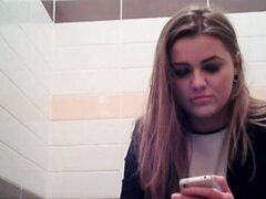 Amateur girl is playing with phone pissing on toilet