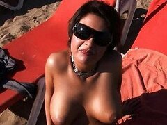 Busty Brunette MILF Flashes her Round Jugs on a Nudist Beach