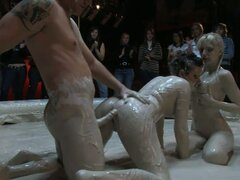 Two spoiled hussies and horny dude mess around in mud in front of people