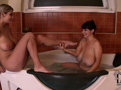 Lesbian babes with enormous natural racks having fun in hot tub